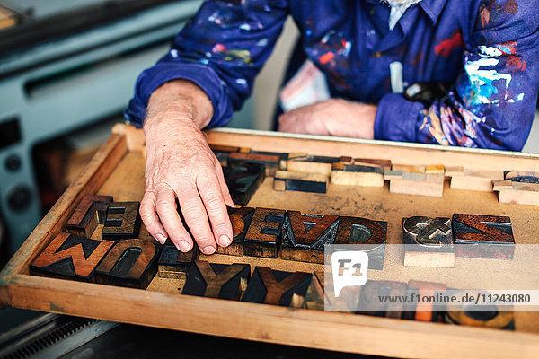 Leitender Handwerker greift nach hölzernen Buchdruckbuchstaben  Mittelteil