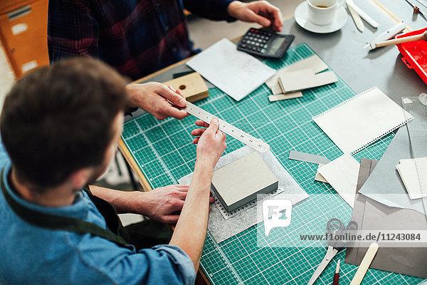Junger Handwerker übergibt Metalllineal an Freund im Druckatelier  erhöhte Ansicht