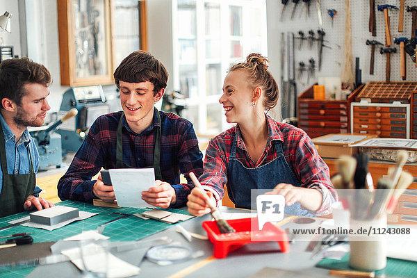 Junge Handwerkerin hält Pinsel und lacht und lächelt mit zwei jungen Handwerkern im kreativen Druckatelier