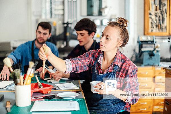 Junge Handwerkerin hält Kaffeetasse und greift nach dem Pinsel im kreativen Druckatelier  im Hintergrund arbeiten zwei junge Handwerker