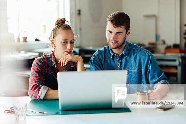 Junger Handwerker und Handwerkerin betrachtet Laptop in Druckatelier-Werkstatt