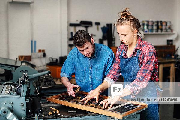 Junge Handwerker und Handwerkerinnen betrachten Buchdruckbuchstaben in Buchkunstwerkstatt