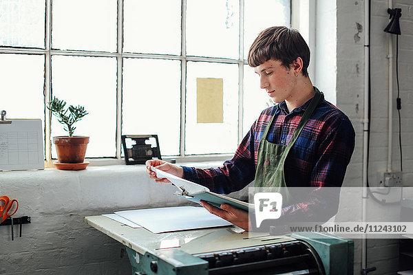 Junger Handwerker am Fenster  an eine Buchdruckmaschine gelehnt und auf die Zwischenablage im Buchkunststudio schauend
