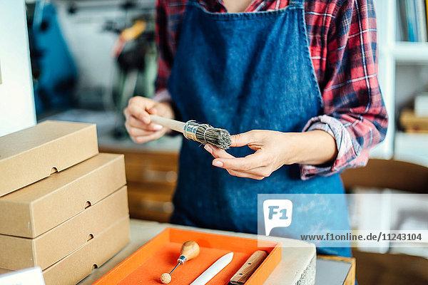 Detail der Hände  die den Pinsel im Buchkunststudio halten