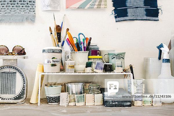 Assortment of art materials and tools in pottery studio