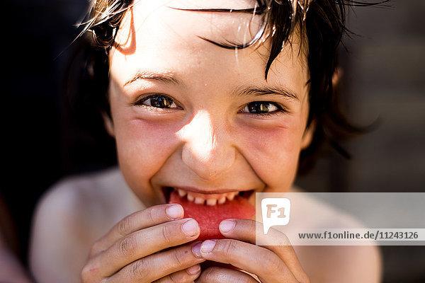 Glücklicher Junge isst am Sommertag Wassermelone