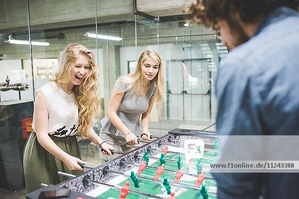 Co-workers playing foosball at break