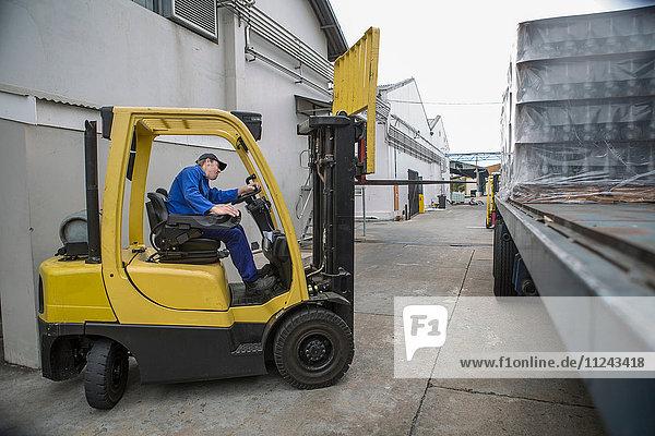 Gabelstaplerfahrer lädt Palette in Verpackungsfabrik auf Lkw