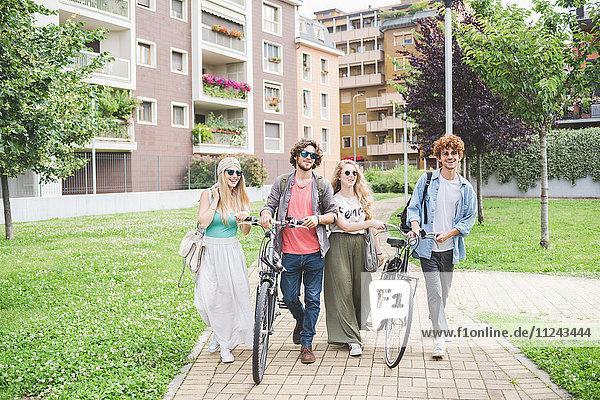 Freunde  die mit dem Fahrrad im Park spazieren gehen.