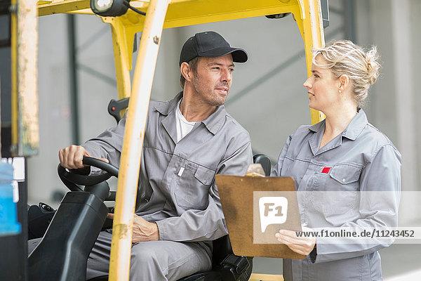 Fabrikleiter mit Zwischenablage im Gespräch mit Gabelstaplerfahrer in Verpackungsfabrik