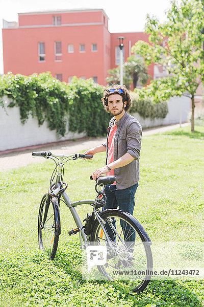 Mann mit Fahrrad im Park