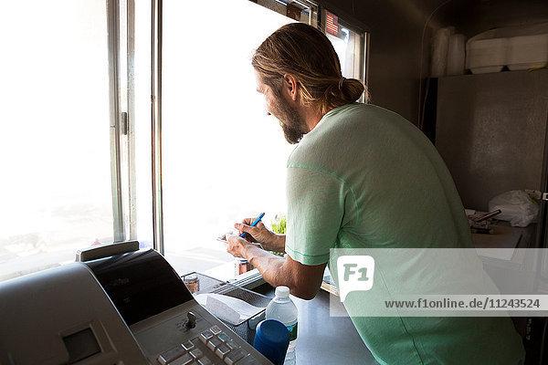 Mann im Fast-Food-Anhänger  lehnt sich durch die Luke  nimmt Kundenbestellung entgegen  Rückansicht