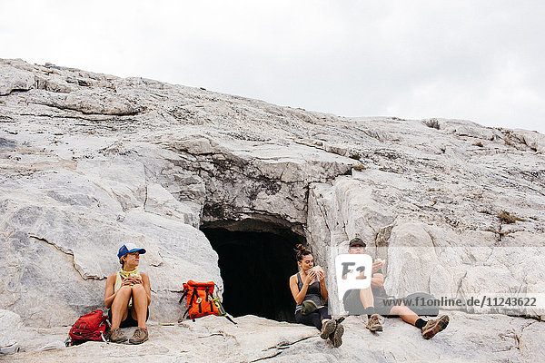 Three hikers taking a break from hike  sitting beside cave  Mineral King  Sequoia National Park  California  USA