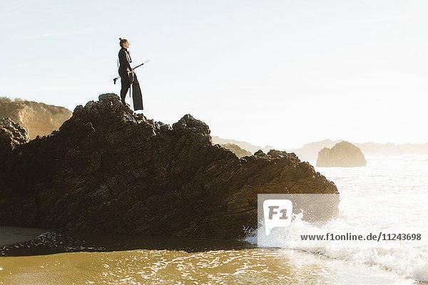 Taucher mit Speer auf Fels stehend  Big Sur  Kalifornien  USA