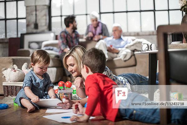 Mutter und Kinder zeichnen zu Hause