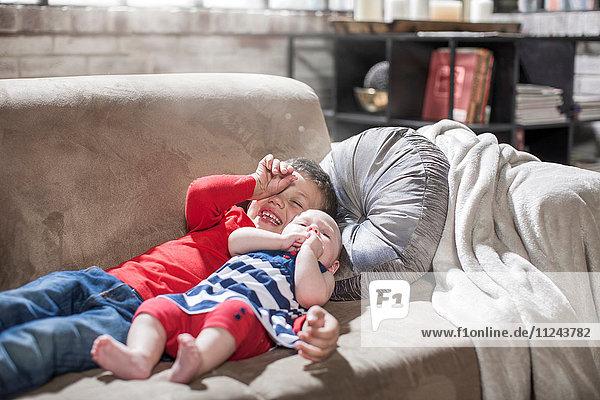 Junge und kleine Schwester liegen zu Hause auf dem Sofa.