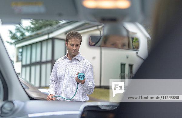 Mann lädt Elektroauto  durch den Innenraum gesehen