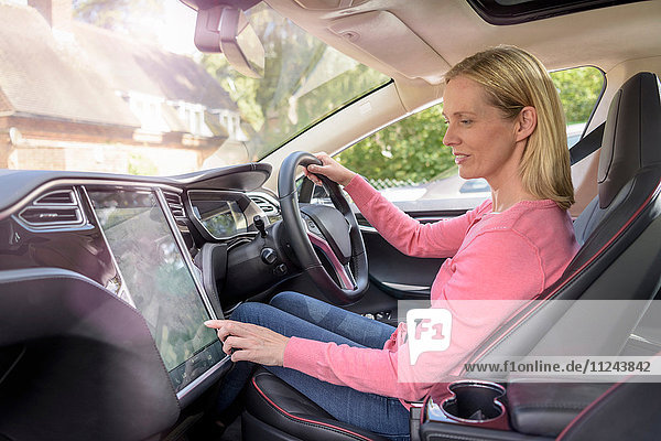 Woman using satellite navigation system in electric car