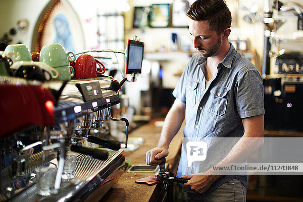 Young man preparing coffee at cafe kitchen counter