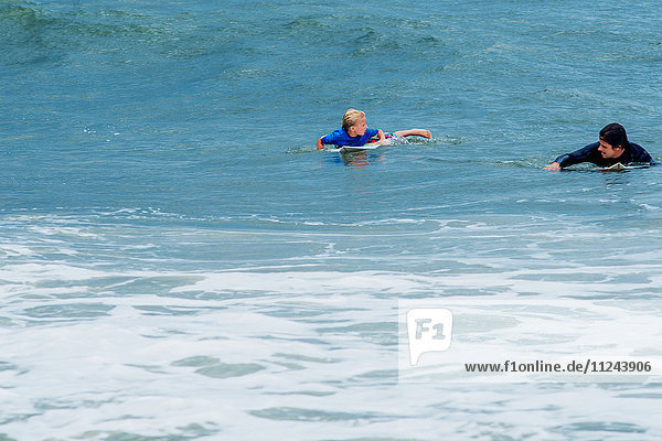 Father and son in sea  paddling on surfboards