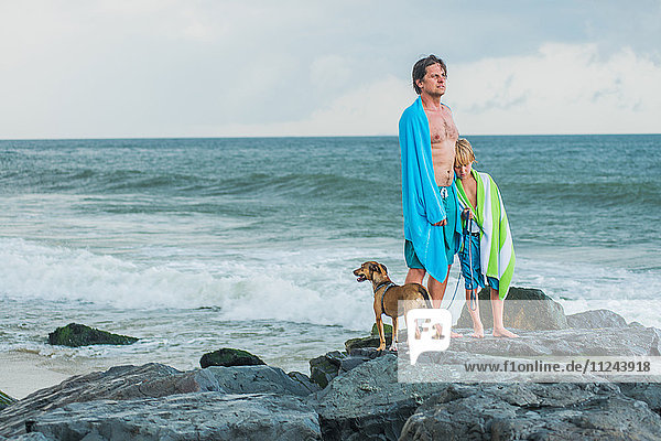 Father and son standing on rocks by sea  beach towels draped around them  pet dog beside them
