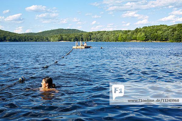 Junge Frau schwimmt im Sebago-See  New York  USA