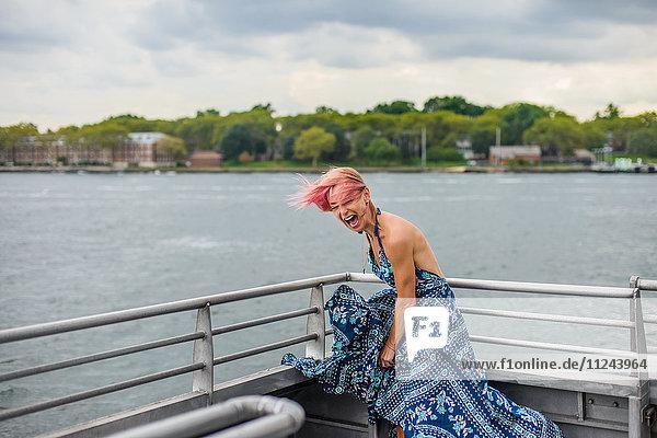 Reife Frau steht auf Boot  lacht  Wind weht Kleid