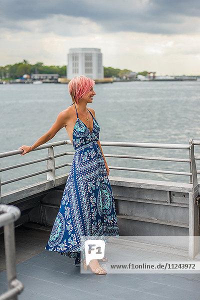 Reife Frau steht auf dem Boot  schaut auf die Aussicht  lächelt