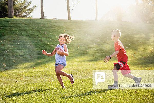Girl and boy playing American football