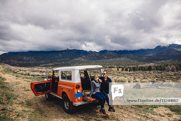Couple with vehicle on scrubland by mountains  Kennedy Meadows  California  USA
