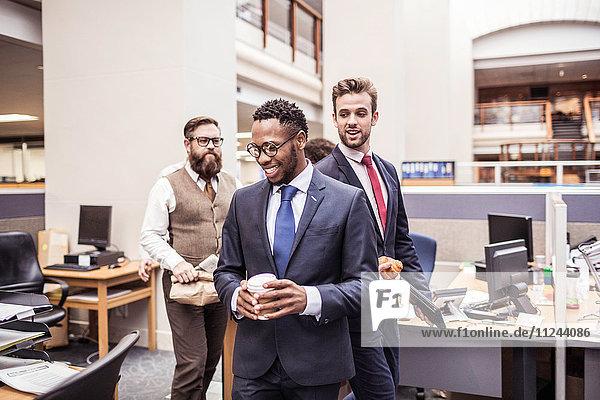 Geschäftsleute gehen mit Kaffee zum Mitnehmen durchs Büro