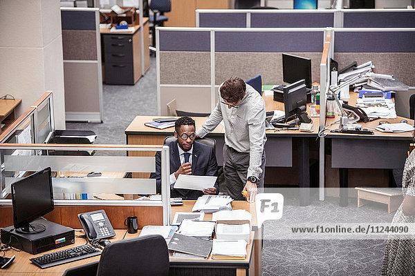 Zwei Geschäftsleute im Gespräch am Büroschreibtisch