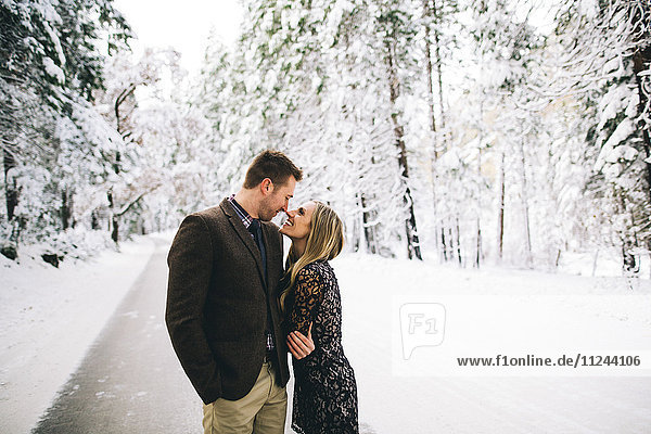 Couple in snow-covered forest face to face smiling
