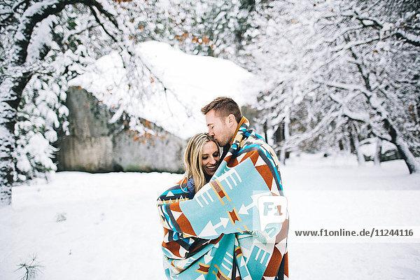 Ehepaar im schneebedeckten Wald in eine Decke gehüllt