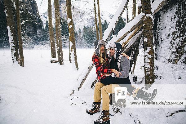 Frau sitzt auf dem Schoss eines Mannes in schneebedeckter Landschaft