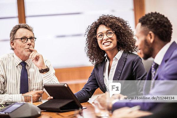 Geschäftsleute nutzen digitales Tablet bei Besprechung am Vorstandstisch
