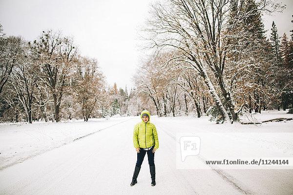 Mann steht auf schneebedeckter Landschaft und schaut in die Kamera