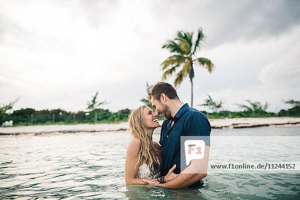 Paar mit tiefer Taille im Wasser  von Angesicht zu Angesicht lächelnd