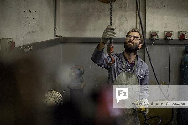 Mann in der Werkstatt mit Kettenzug