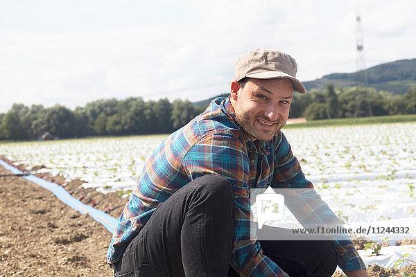 Farmer in field tending to seedlings  looking at camera smiling