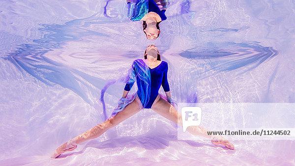 Unterwasseraufnahme eines Mädchens in blauem Trikot und Ballettschuhen mit Blick auf die Wasseroberfläche