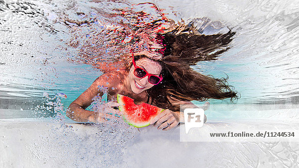Unterwasseraufnahme einer Frau  die eine Sonnenbrille trägt  eine Scheibe Wassermelone isst und lächelt
