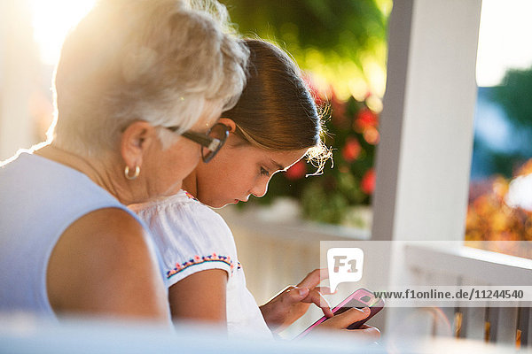 Girl playing smartphone game sitting on grandmother's lap in porch at sunset