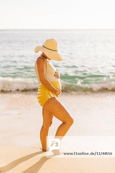 Pregnant mid adult woman wearing swimming costume holding stomach Makua beach  Hawaii  USA