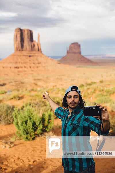 Junger Mann nimmt sich selbst und zeigt auf Sandsteinfelsen  Monument Valley  Arizona  USA