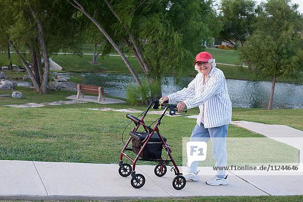 Ältere Frau  die mit Gehhilfe im Freien geht
