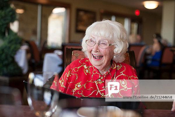 Ältere Frau sitzt am Tisch im Restaurant und lacht