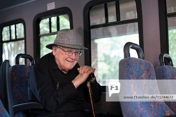 Porträt eines älteren Mannes  der im Zug sitzt und einen Spazierstock hält