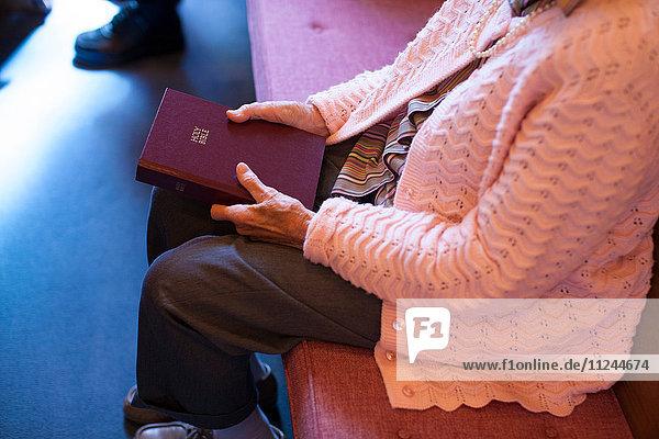 Ältere Frau sitzt in der Kapelle  hält Bibel  niedriger Abschnitt