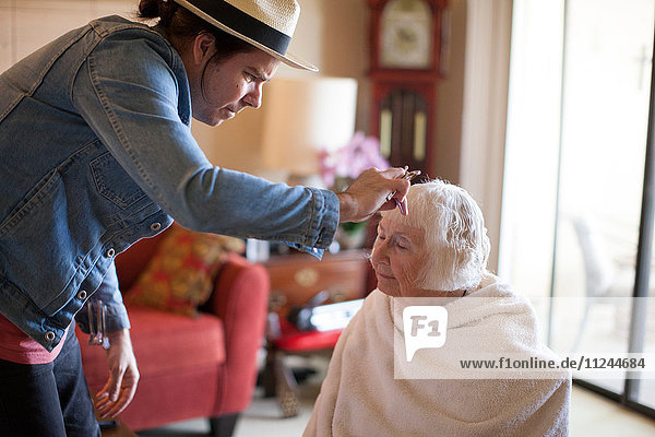 Reifer Mann schneidet älteren Frauen die Haare